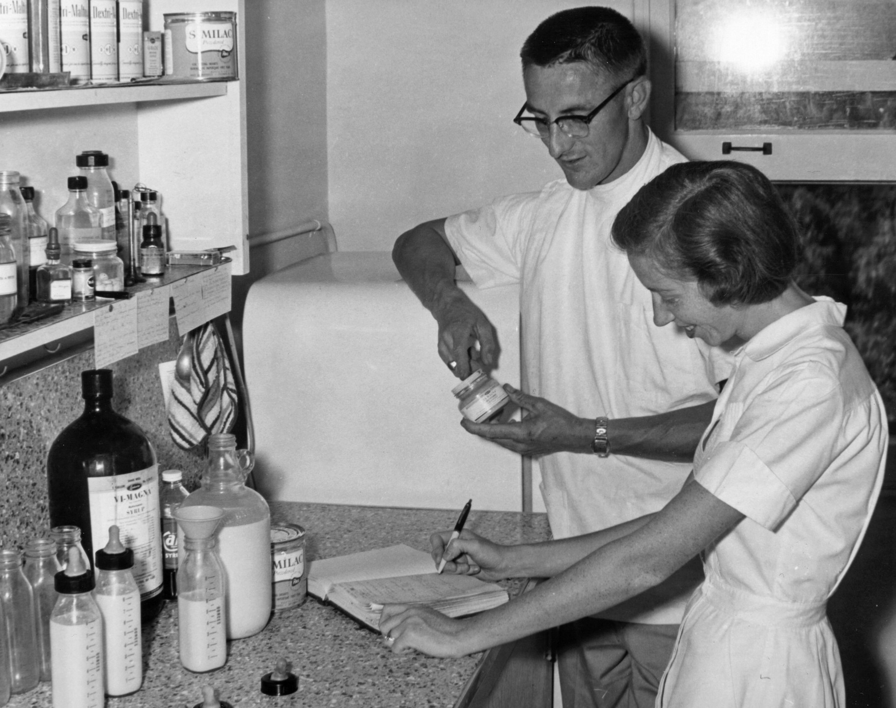 In 1956, the Zoo hired a new veterinarian, Dr. Werner Heuschele, who would be instrumental in establishing innovative veterinary procedures and care methods as exotic veterinary medicine advanced in the 1950s and 1960s. One was participating in the testing and use of the first dart guns invented to deliver anesthetics from a distance. Dr. Heuschele would also become a familiar face who would return to the Zoological Society later to head up conservation research efforts. Here (in 1958), he reviews records with Mrs. Barbara